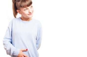 girl touching her stomach on a white background
