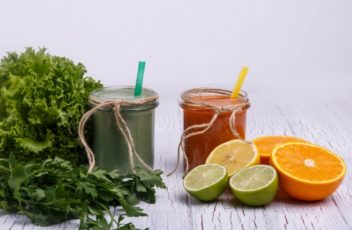 green-and-orange-detox-coctails-stands-on-white-table-with-fruits-and-vegetables_1304-3507