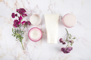 high-angle-view-of-beauty-creams-and-flowers-on-marble_23-2147879025